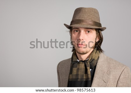 Portrait of a young man in a jacket and hat - stock photo