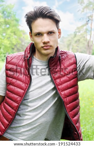 portrait of a young man in a waistcoat on nature - stock photo