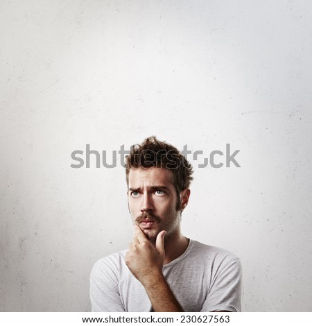 Portrait of a young man in doubt - stock photo