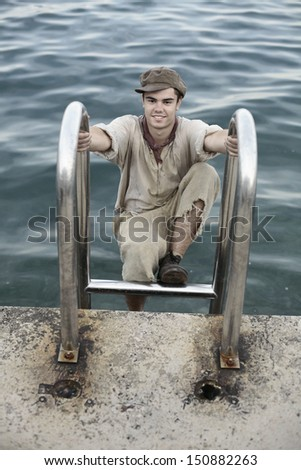 portrait of a young man in old retro clothes and cap climbing up on stairs  by the water, an apprentice looking poor and dirty - stock photo
