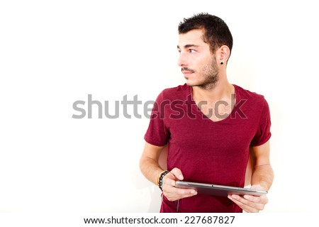 Portrait of a young man in red shirt using tablet.  - stock photo