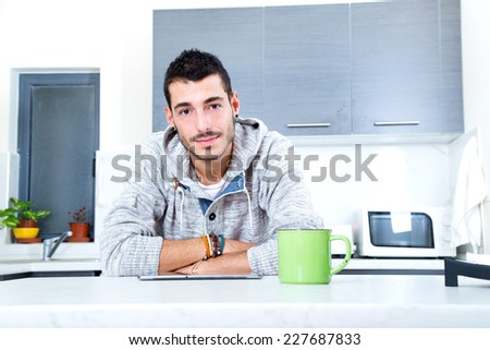 Portrait of a young man in the kitchen with a tablet.  - stock photo
