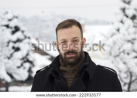 Portrait of a young man in the winter raising an eyebrow - stock photo