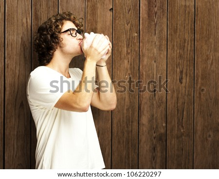 portrait of a young man kissing a piggy bank against a wooden wall - stock photo