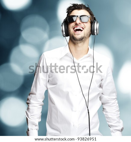 portrait of a young man listening to music with headphones against an abstract background - stock photo