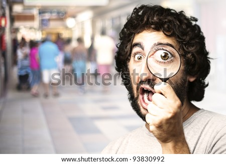 portrait of a young man looking through a magnifying glass against a crowded place - stock photo