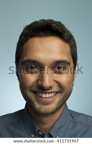 Portrait of a young man making funny face against blue backgroun - stock photo