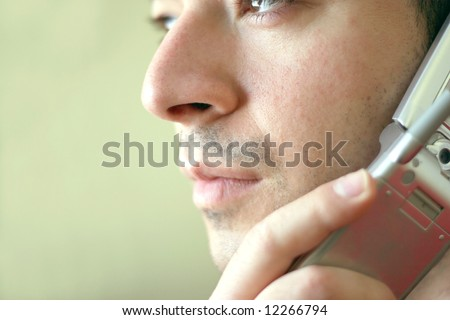 Portrait of a young man on his cell phone.  He is listening with a  serious look of concern on his face. - stock photo