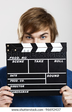 Portrait of a young man peeking behind a clapboard, over a gray background - stock photo