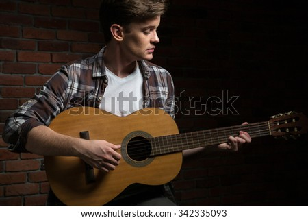 Portrait of a young man playing on the guitar with brick wall on background - stock photo