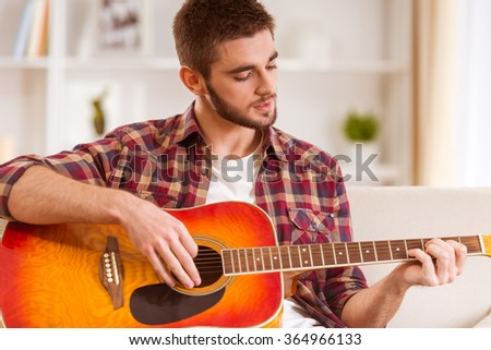 Portrait of a young man playing the guitar at home - stock photo