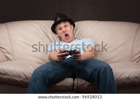 portrait of a young man playing video games on gray background - stock photo