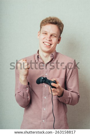 portrait of a young man plays on the joystick to the console - stock photo