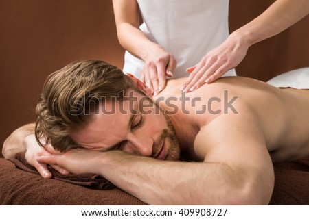 Portrait Of A Young Man Receiving Back Massage At A Beauty Spa - stock photo