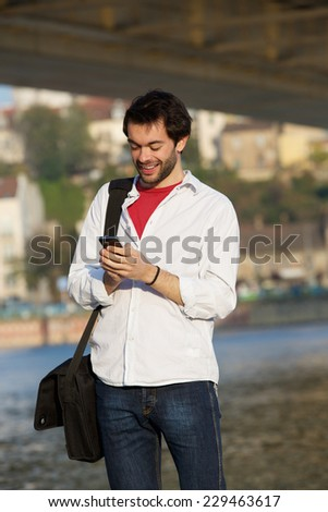 Portrait of a young man sending text message on mobile phone outdoors - stock photo