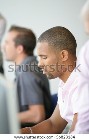 Portrait of a young man sitting at a desk - stock photo