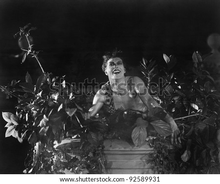 Portrait of a young man sitting on a wall with lowers and plants and smiling - stock photo