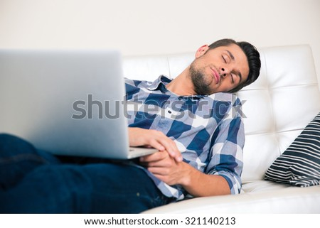 Portrait of a young man sleeping with laptop on the sofa at home - stock photo