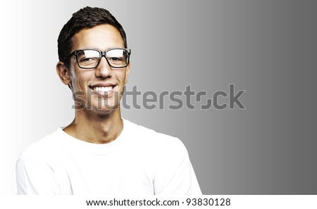portrait of a young man smiling against a grey background - stock photo