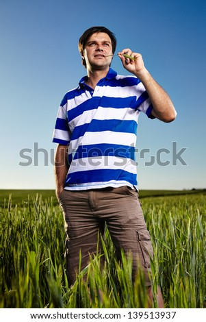 Portrait of a young man standing in a wheat field - stock photo