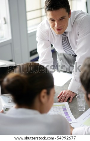 Portrait of a young man standing in front of a desk - stock photo