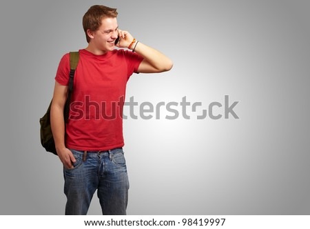 portrait of a young man talking on a mobile over a grey background - stock photo