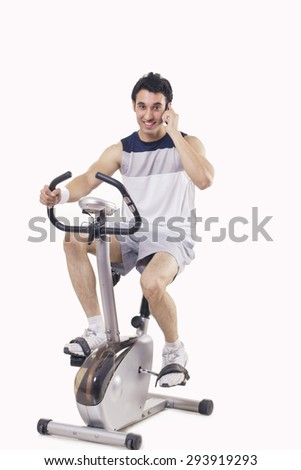 Portrait of a young man talking on mobile phone while exercising over white background - stock photo