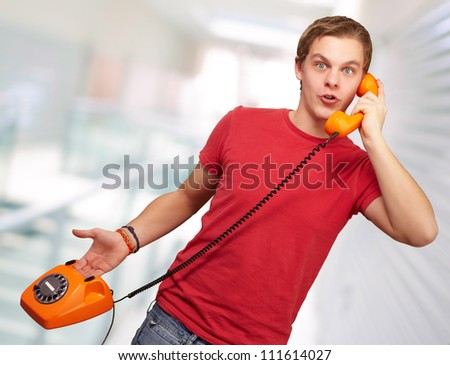 Portrait of a young man talking on vintage phone, indoor - stock photo