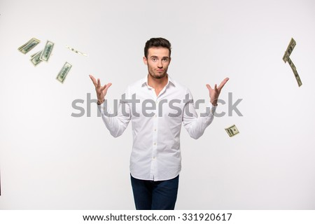 Portrait of a young man throwing money in the air isolated on a white background - stock photo