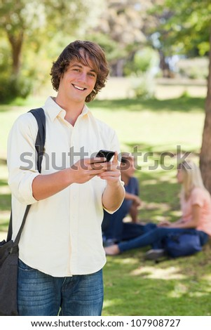 Portrait of a young man using a smartphone in a park with friends in background - stock photo