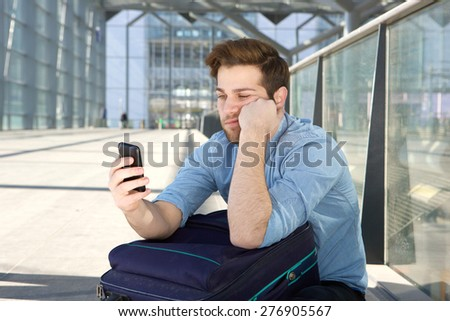 Portrait of a young man waiting at airport with bored expression on face - stock photo