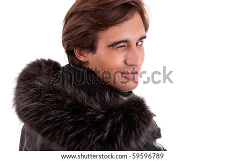 Portrait of a young man winking from back, in autumn/winter clothes, isolated on white. Studio shot - stock photo