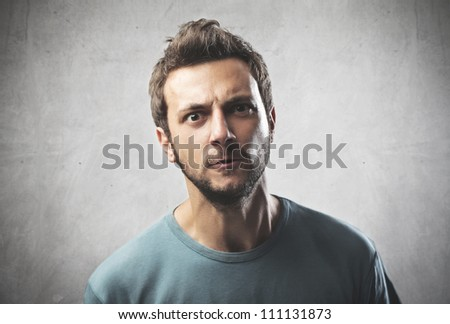 Portrait of a young man with aggressive expression - stock photo