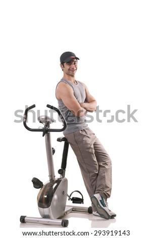 Portrait of a young man with arms crossed leaning on exercise bike over white background - stock photo