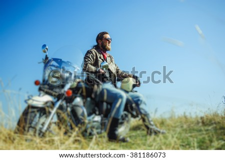 Portrait of a young man with beard sitting on his cruiser motorcycle and smiling. Man is wearing leather jacket and blue jeans. Low point of view. Tilt shift lens blur effect - stock photo