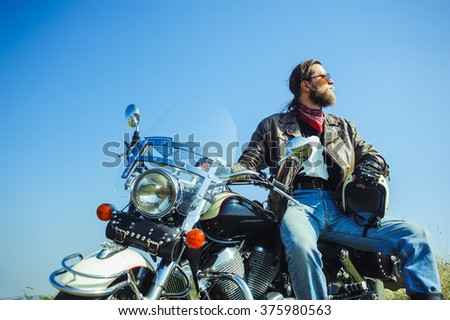 Portrait of a young man with beard sitting on his cruiser motorcycle. Man is wearing leather jacket and blue jeans. Low point of view - stock photo
