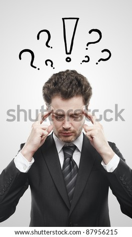 Portrait of a young man with exclamation mark and question marks above his head. Conceptual image of a open minded man. On a gray background - stock photo