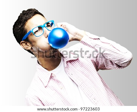 portrait of a young man with glasses inflating a blue balloon against a white background - stock photo