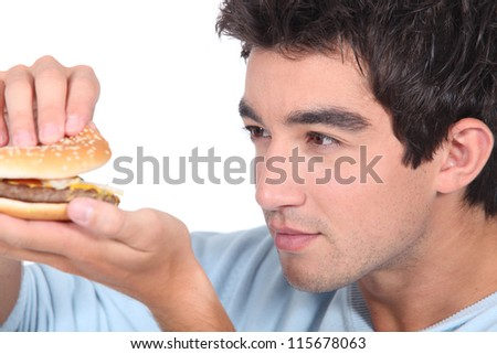 portrait of a young man with hamburger - stock photo