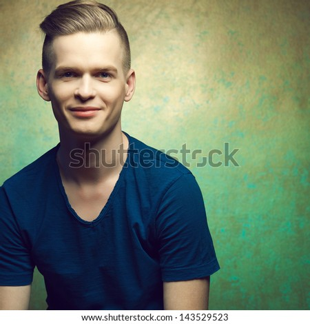 Portrait of a young man with very handsome face in blue casual t-shirt and stylish haircut posing over golden-turquoise  background and smiling. Perfect skin and hair. Copy-space. Studio shot - stock photo