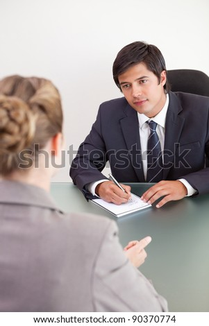 Portrait of a young manager interviewing a female applicant in his office - stock photo