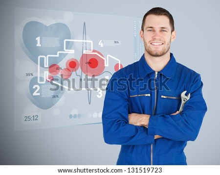 Portrait of a young mechanic with futuristic interface with engine next to him - stock photo