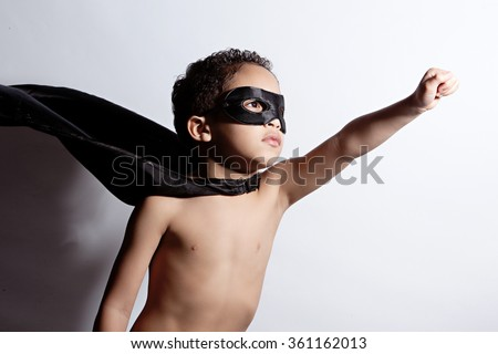 Portrait of a young, mixed race boy dressed as a superhero. - stock photo