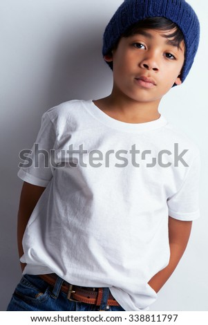 Portrait of a young mixed race boy wearing a white tee shirt and a knit hat.   - stock photo