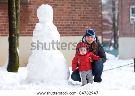 Portrait of a young mother with her baby sitting next to a snowman - stock photo