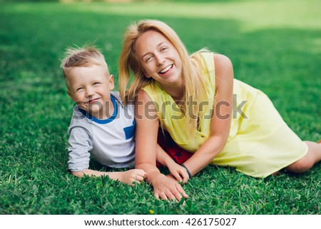 Portrait of a young mother with her son lying on a grass. - stock photo