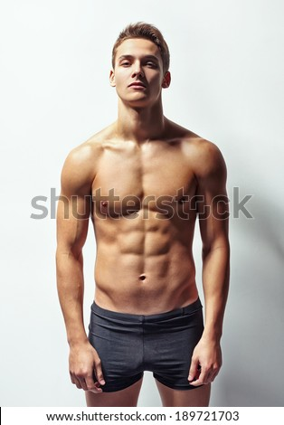 Portrait of a young muscular man in underwear against white wall - stock photo