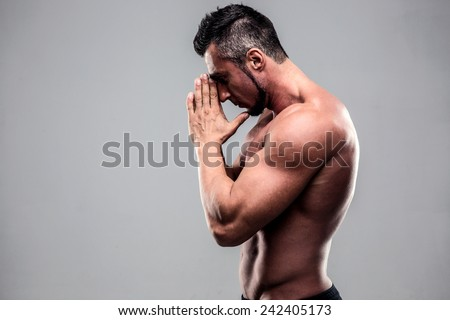 Portrait of a young muscular man praying over gray background - stock photo