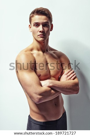 Portrait of a young muscular man with naked torso standing with arms crossed against white wall - stock photo