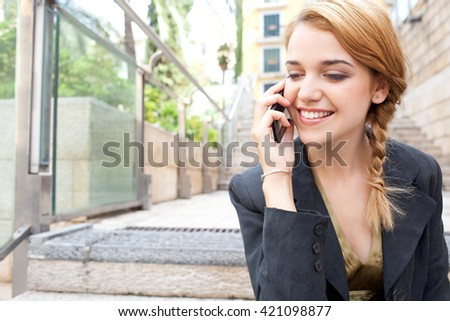 Portrait of a young office business woman using smart phone in call conversation, with technology sitting in city stairs, outdoors. Professional woman speaking on cell phone, smiling, sunny exterior. - stock photo